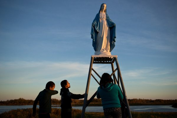 Attawapiskat, Ontario, Canada. Young people play at a statue of the Virgin Mary near the St. Francois-xavier Catholic Church on the shores of the Attawapiskat river. The community has a complicated history with the Catholic church with many of its members subjected to horrible abuses while in the Catholic run residential school system.  Attawapiskat is an isolated First Nation community  located in northern Ontario, Canada, at the mouth of the Attawapiskat River on James Bay. On April 9, 2016, the community of approximately 2000 people declared a state of emergency after being overwhelmed with attempted suicides, over 100 attempts in a ten month period. October 7, 2016. David Maurice Smith/Oculi.