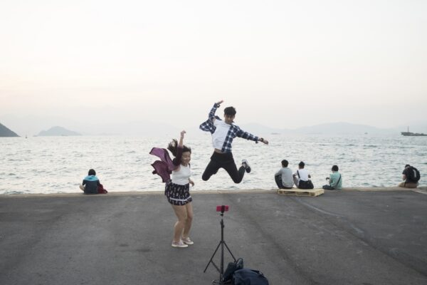 "Hong Kong (Hong Kong SAR, China); Date (11, 03, 2016); A young couple practicing jumping in front of the camera; ""Instagram pier"" is a public cargo pier located on the west side of Hong Kong island; here locals gather for fishing, excercising or walking their pets. More recently the Pier has raised to fame as the ""instagram Pier"", where young Hong Kongers and instagrammers come for selfies and scenic photos. I have recently begun curating its ""instagram""  dedicated account (@insta_pier)."