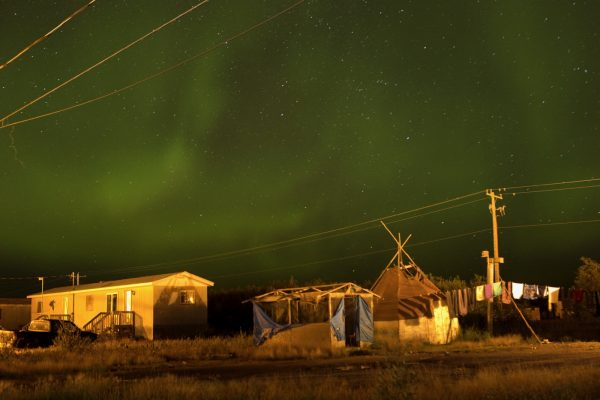 Attawapiskat, Ontario, Canada. The Northern lights, almost overpowering in their physical beauty, fill the night sky over Attawapiskat. Cree legends state that the lights are spirits of the ancestors celebrating life and showing the living that they are all part of creation. Their dancing forms a laneway for the souls as they travel to the next realm. It is said that when Cree are living the right way and conducting ceremonies and dances, the spirits of Cree ancestors celebrate in the heavens. Attawapiskat is an isolated First Nation community  located in northern Ontario, Canada, at the mouth of the Attawapiskat River on James Bay. On April 9, 2016, the community of approximately 2000 people declared a state of emergency after being overwhelmed with attempted suicides, over 100 attempts in a ten month period. August 27, 2016. David Maurice Smith/Oculi.