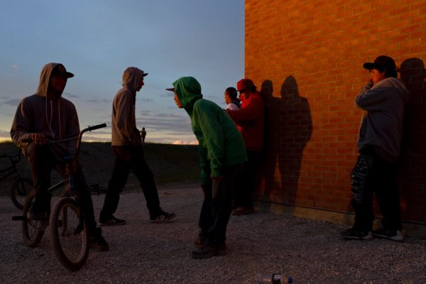 "Attawapiskat, Ontario, Canada. Young people gather at dusk outside the Kattawapiskak Elementary School. The suicide crisis that came to light in 2016 was largely impacting youth with the majority of the attempts amongst teenagers. One elder in the community cited a growing disconnect between traditional ways and the younger generation, amplified by the many challenges associated with living in a remote community. ""It is important now for young people to understand the colonial policies that have left their communities disconnected"" she said. ""Only if they can understand what people went through can they articulate why their lives may be in chaos."". .  Attawapiskat is an isolated First Nation community  located in northern Ontario, Canada, at the mouth of the Attawapiskat River on James Bay. On April 9, 2016, the community of approximately 2000 people declared a state of emergency after being overwhelmed with attempted suicides, over 100 attempts in a ten month period. August 20, 2016. David Maurice Smith/Oculi."